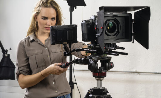 Beautiful woman operating a video camera rig